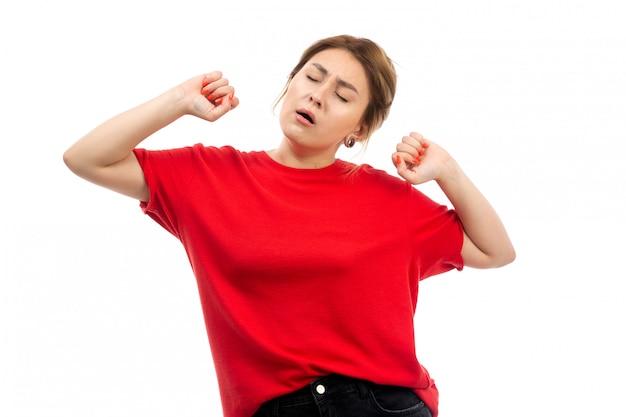 Ein junges attraktives mädchen der vorderansicht im roten t-shirt, das schwarze jeans trägt, die niesend auf dem weiß schlafen wollen Kostenlose Fotos
