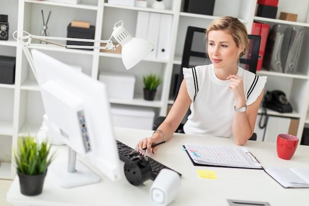 Ein junges blondes mädchen sitzt an einem computertisch im büro, hält einen bleistift in der hand und druckt auf der tastatur. Premium Fotos