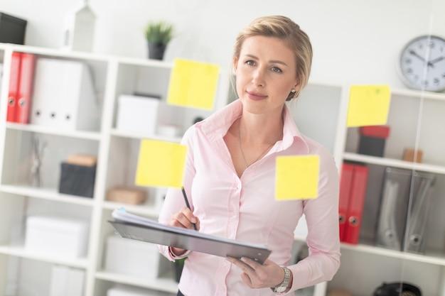 Ein junges blondes mädchen steht im büro neben einem transparenten brett mit aufklebern und hält dokumente und einen bleistift in den händen. Premium Fotos