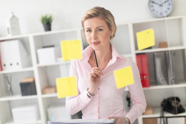 Ein junges blondes mädchen steht im büro neben einem transparenten brett mit aufklebern und hält dokumente Premium Fotos