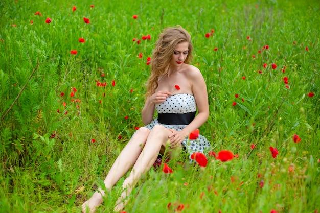 Ein junges langhaariges mädchen genießt an einem heißen sommertag die farben der natur auf einem blühenden mohnfeld. Premium Fotos