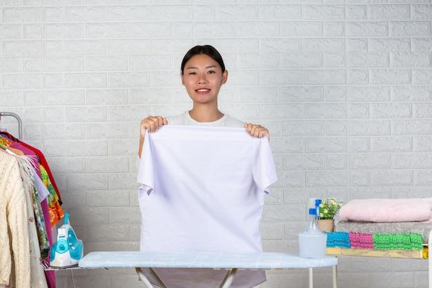 Ein junges mädchen, das ein hemd auf ihrem bügelbrett mit einem weißen ziegelstein vorbereitet. Kostenlose Fotos