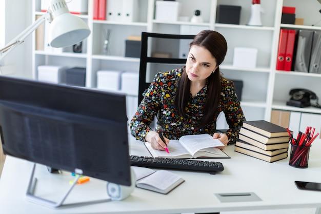 Ein junges mädchen, das im büro am computertisch sitzt und mit einem buch arbeitet. Premium Fotos