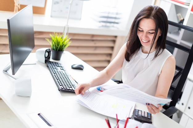 Ein junges mädchen, das im büro an einem computertisch sitzt und mit dokumenten und einem taschenrechner arbeitet. Premium Fotos