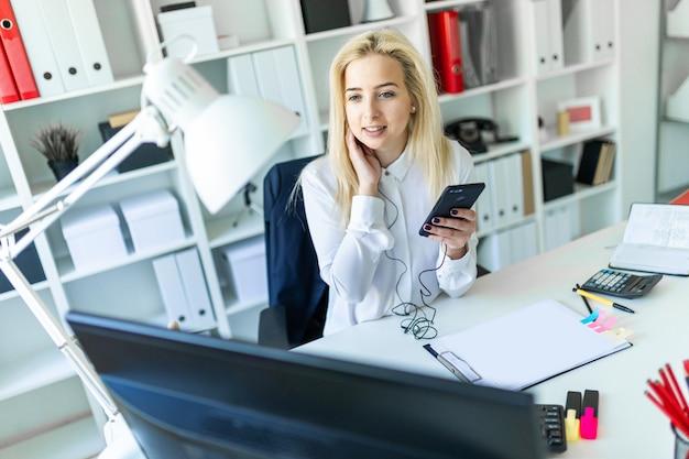 Ein junges mädchen im büro sitzt an einem schreibtisch und hält ein telefon in der hand Premium Fotos