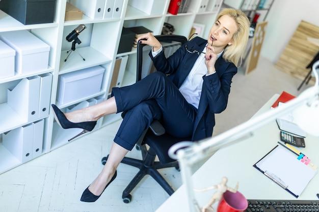 Ein junges mädchen im büro sitzt auf einem stuhl und wirft die beine auf die armlehne. Premium Fotos