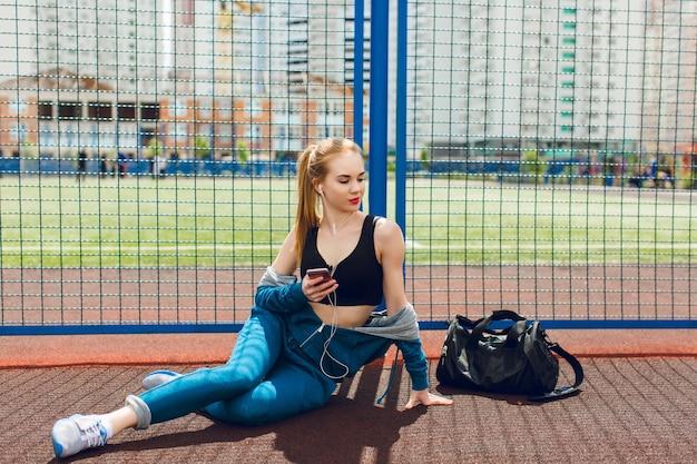 Ein junges mädchen in einem blauen sportanzug mit einem schwarzen oberteil sitzt in der nähe des zauns auf dem stadion. sie hört die musik mit kopfhörern und schaut weit weg. Kostenlose Fotos