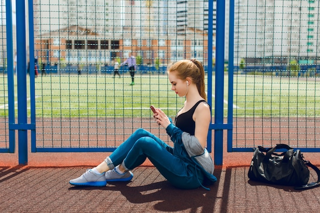 Ein junges mädchen in einem blauen sportanzug mit einem schwarzen oberteil sitzt in der nähe des zauns auf dem stadion. sie hört die musik mit kopfhörern. Kostenlose Fotos