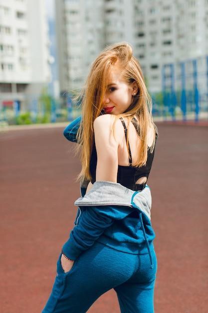 Ein junges mädchen in einem blauen trainingsanzug und einem schwarzen oberhemd steht auf dem stadion. sie hat lange haare und eine gute figur. sie lächelt in die kamera. Kostenlose Fotos