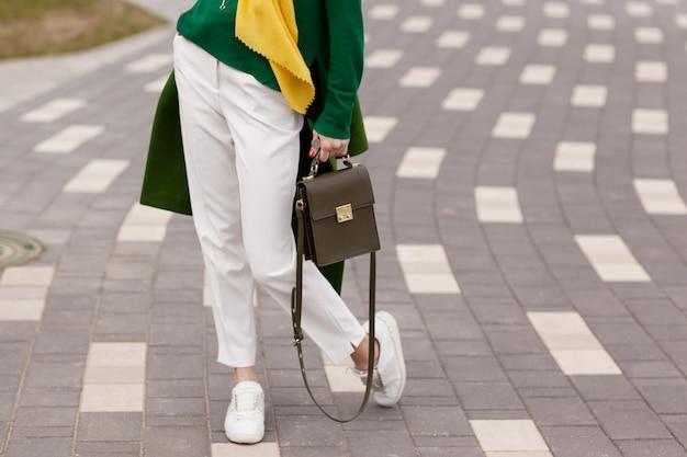 Ein junges mädchen in weißer hose, warmes grünes fell Premium Fotos