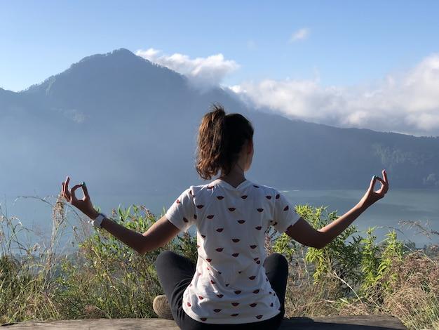 Ein junges mädchen meditiert am berg Premium Fotos