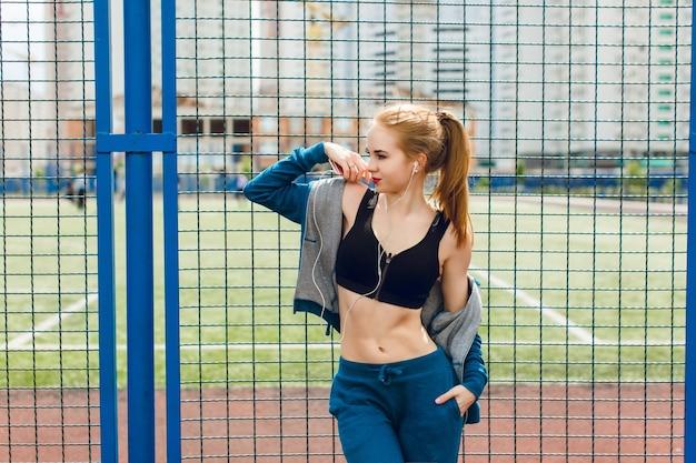 Ein junges mädchen mit einer attraktiven figur steht in der nähe des blauen zauns auf dem stadion. sie trägt einen blauen sportanzug mit schwarzem oberteil. sie hört die musik mit kopfhörern und schaut weit weg. Kostenlose Fotos