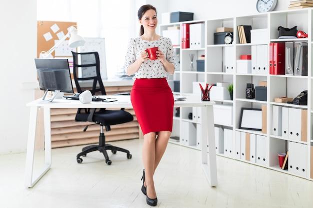 Ein junges mädchen setzte sich auf einen computertisch im büro und hielt eine rote tasse in der hand. Premium Fotos