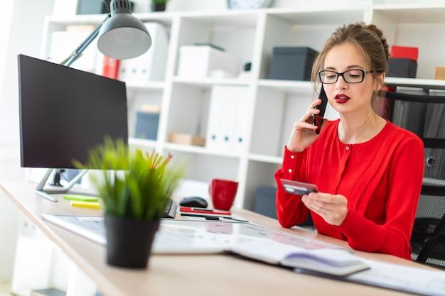 Ein junges mädchen sitzt am schreibtisch im büro und hält eine bankkarte und ein telefon in der hand. Premium Fotos