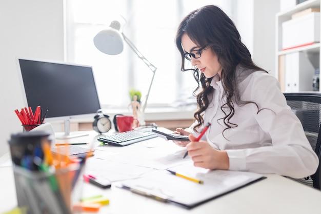 Ein junges mädchen sitzt am schreibtisch und arbeitet mit einem taschenrechner und dokumenten. Premium Fotos