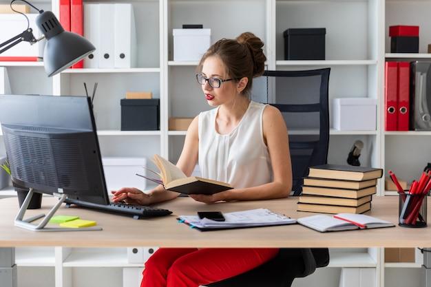 Ein junges mädchen sitzt an einem computertisch und hält ein offenes buch in den händen. Premium Fotos