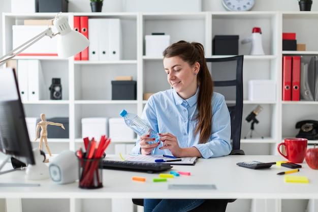 Ein junges mädchen sitzt an einem tisch im büro und hält eine flasche wasser in der hand. Premium Fotos