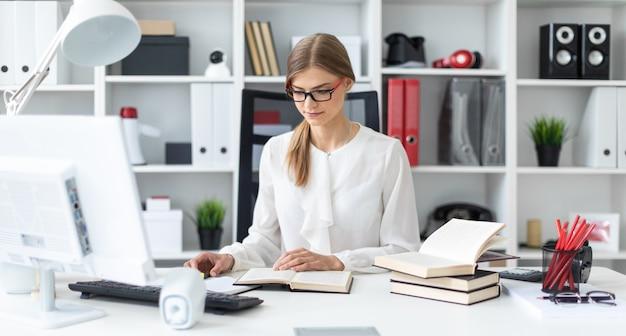 Ein junges mädchen sitzt an einem tisch im büro und hält eine gelbe markierung in der hand. Premium Fotos
