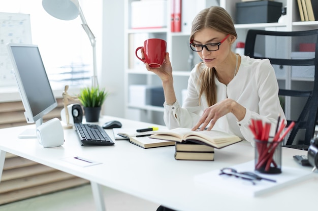 Ein junges mädchen sitzt an einem tisch im büro und hält eine rote tasse in der hand und liest ein buch. Premium Fotos
