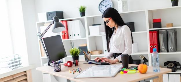 Ein junges mädchen steht neben einem tisch und druckt auf der tastatur, bevor das mädchen eine magnettafel und markierungen trägt Premium Fotos