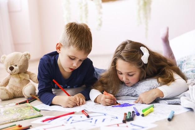 Ein junges mädchen und ein junge zeichnen in malbüchern, die im raum auf dem boden liegen Kostenlose Fotos
