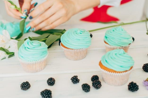 Ein junges mädchen verziert cupcakes mit frischen beeren und blumen Premium Fotos