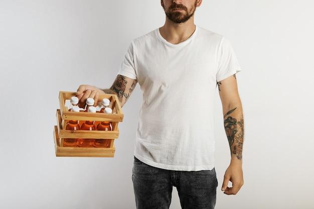 Ein junges modell mit tätowierungen und bart, das ein sixpack unbeschrifteter orangefarbener getränke auf weiß hält Kostenlose Fotos