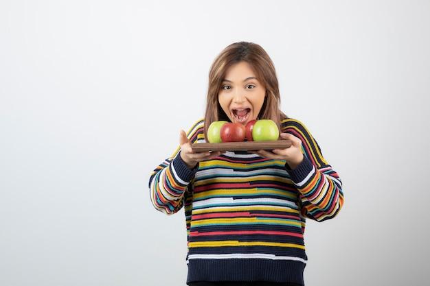 Ein junges niedliches frauenmodell, das eine hölzerne platte mit bunten frischen äpfeln hält. Kostenlose Fotos