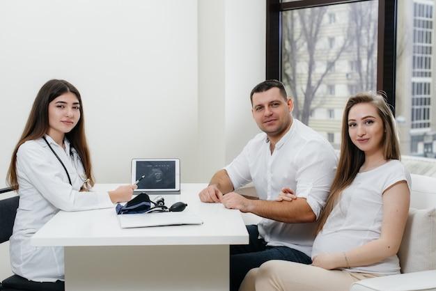 Ein junges paar, das darauf wartet, dass ein baby nach einem ultraschall einen frauenarzt konsultiert. schwangerschaft und gesundheitsversorgung Premium Fotos