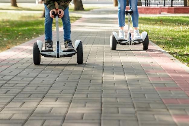 Ein junges paar, das ein hoverboard in einem park reitet Premium Fotos