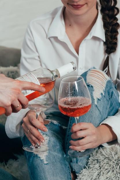 Ein junges paar in blue jeans und weißen hemden trinkt roséwein Premium Fotos