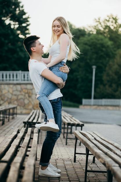 Ein junges paar in der liebe, die auf der bank im park aufwirft Premium Fotos