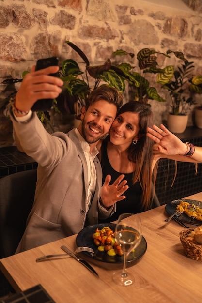 Ein junges paar verliebt in ein restaurant, spaß beim gemeinsamen essen haben, valentinstag feiern, ein souvenir-selfie machen Premium Fotos