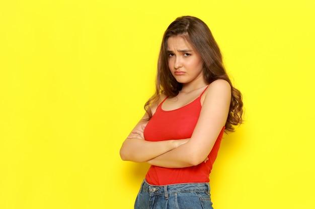 Ein junges schönes mädchen der vorderansicht im roten hemd und in den blauen jeans, die mit dem verrückten und traurigen ausdruck aufwerfen Kostenlose Fotos