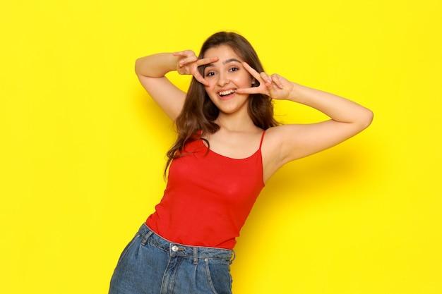 Ein junges schönes mädchen der vorderansicht im roten hemd und in den blauen jeans, die mit lustigem ausdruck aufwerfen Kostenlose Fotos