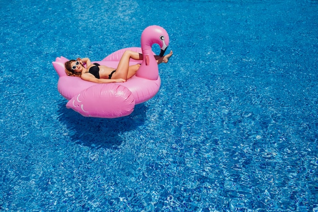 Ein junges schönes mädchen mit einer schönen figur in einem schwarzen badeanzug und einer sonnenbrille Premium Fotos