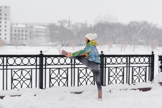 Ein junges sportliches mädchen wärmt sich auf, bevor es an einem frostigen tag rennt. fitness, laufen. Premium Fotos