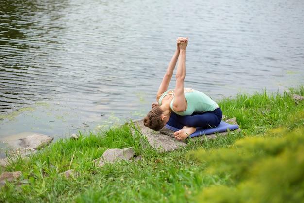 Ein junges sportmädchen übt yoga auf einem grünen rasen am fluss, yoga assans haltung. meditation und einheit mit der natur Premium Fotos