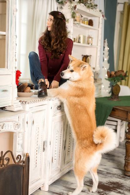 Ein junges trauriges mädchen mit einem gehorsamen hund sitzt auf einer kommode am fenster Premium Fotos