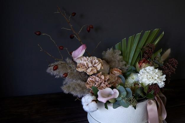 Ein kasten mit einem weinleseblumenstrauß auf einem dunklen hintergrund Premium Fotos