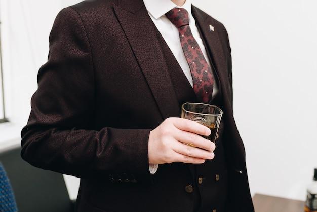 Ein kaukasischer mann, der einen anzug trägt und ein glas hält Premium Fotos
