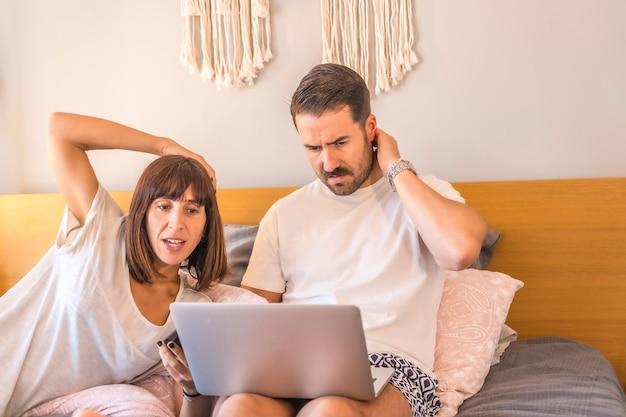 Ein kaukasisches paar auf dem bett mit einem computer und einem telefon, das eine reservierung in einem hotel oder flug vornimmt, urlaub organisiert, neue technologien in der familie. junge fragt sich, welche reise zu wählen Premium Fotos