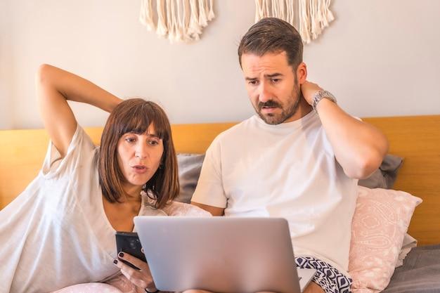 Ein kaukasisches paar auf dem bett mit einem computer und einem telefon, das eine reservierung in einem hotel oder flug vornimmt, urlaub organisiert, neue technologien in der familie. mit zweifel, welche reise zu wählen Premium Fotos