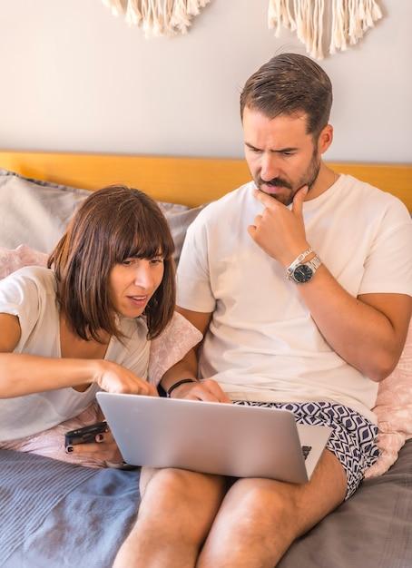 Ein kaukasisches paar auf dem bett mit einem computer und einem telefon, das eine reservierung in einem hotel oder flug vornimmt, urlaub organisiert, neue technologien in der familie. suche nach den besten angeboten Premium Fotos