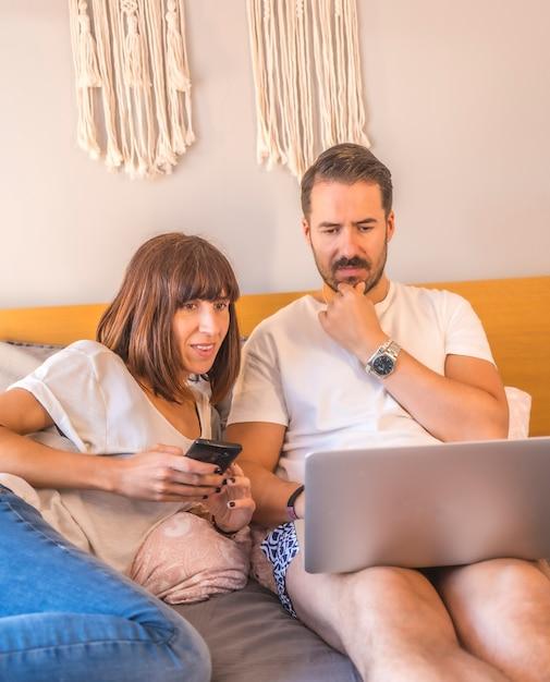 Ein kaukasisches paar auf dem bett mit einem computer und einem telefon, das eine reservierung in einem hotel oder flug vornimmt, urlaub organisiert, neue technologien in der familie. Premium Fotos