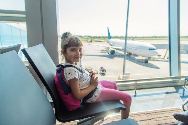 Ein kind am flughafen auf dem hintergrund des flugzeugs Premium Fotos
