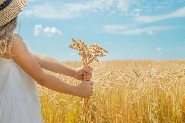 Ein kind auf einem weizengebiet. Premium Fotos