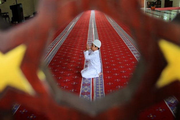 Ein kind betet in der moschee Premium Fotos