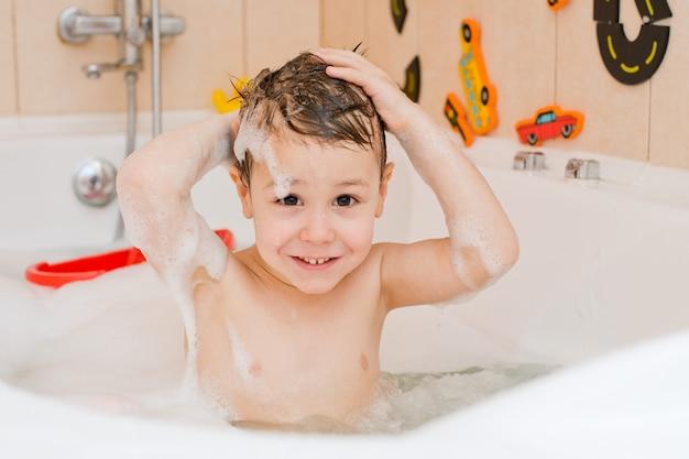 Ein kind, das ein bad mit schaum nimmt Premium Fotos