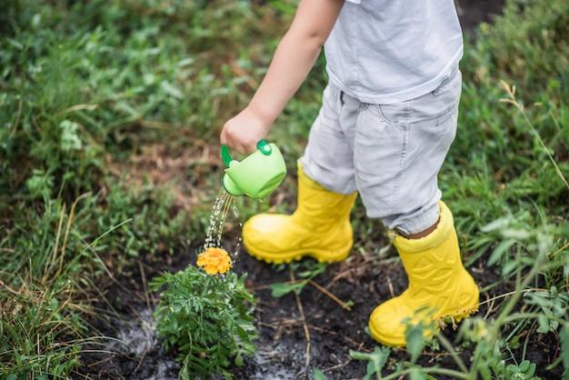 Ein kind im garten, der blumen mit einer gießkanne gießt. Premium Fotos